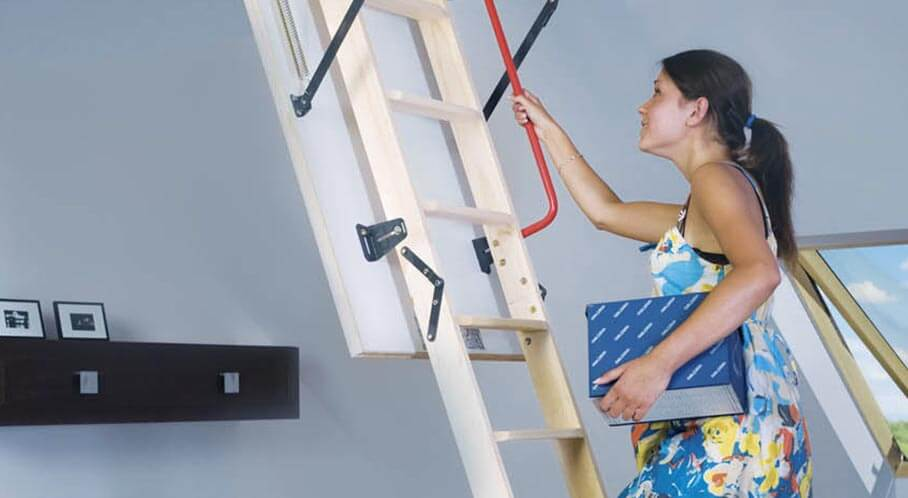 Extended loft ladder and woman climbing