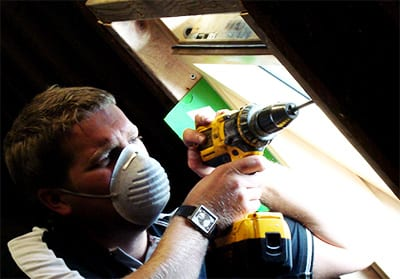 fitter working in loft with face mask