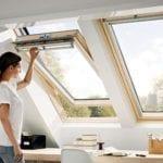 woman opening VELUX roof window