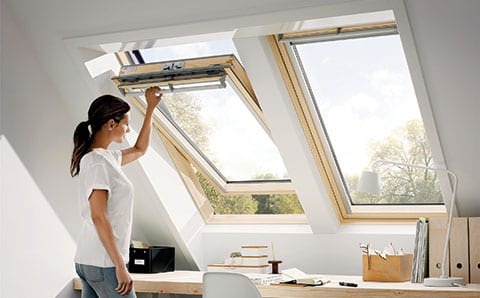 woman opening VELUX roof window